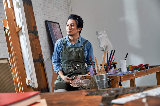 Focused male artist in apron holding palette and looking at picture in studio — Stock Photo