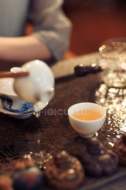 Cropped shot of woman pouring tea in porcelain cup — Stock Photo