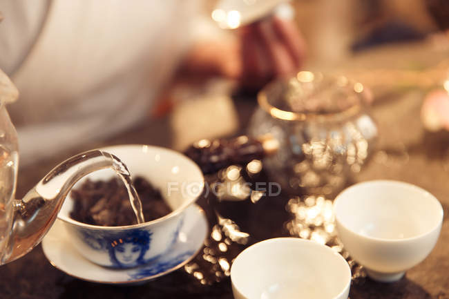 Cropped shot of woman pouring water into porcelain cup with tea — Stock Photo