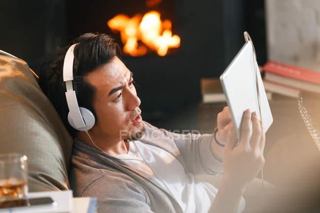 Vista laterale di bello asiatico uomo in cuffie utilizzando digitale tablet a casa — Foto stock