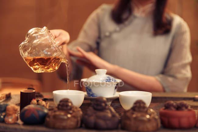Vista parcial cercana de la mujer que vierte té en tazas blancas - foto de stock