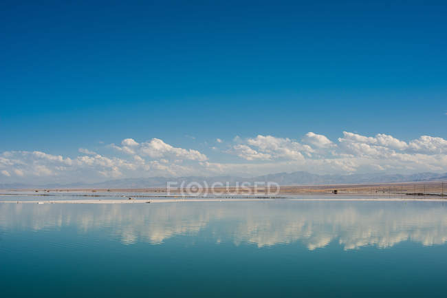 Amazing landscape with blue sky and white clouds reflected in calm water — Stock Photo