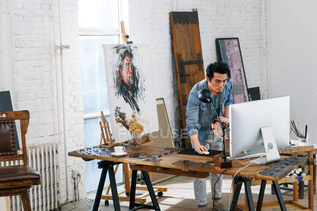 Young male artist holding palette and using desktop computer in studio — Stock Photo