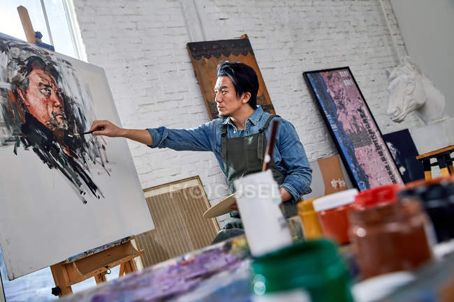 Serious young asian artist painting portrait in art studio — Stock Photo