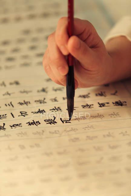 Зграбований постріл жінки з пензлем для каліграфії та письмом китайських символів. — стокове фото