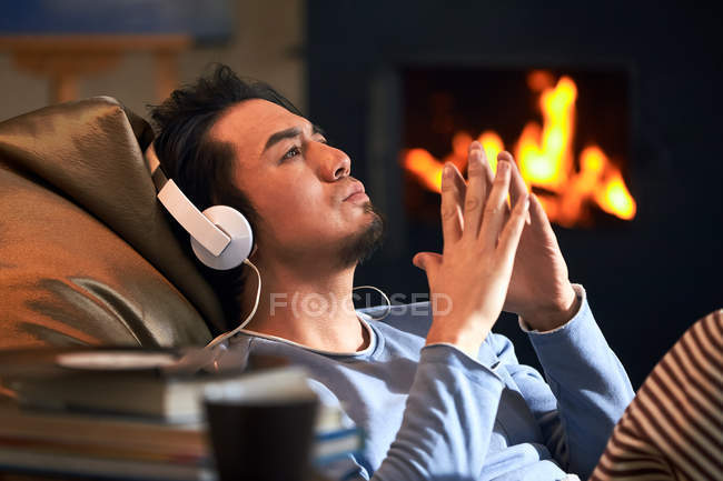 Side view of handsome relaxed man listening music in headphones and looking up at home — Stock Photo