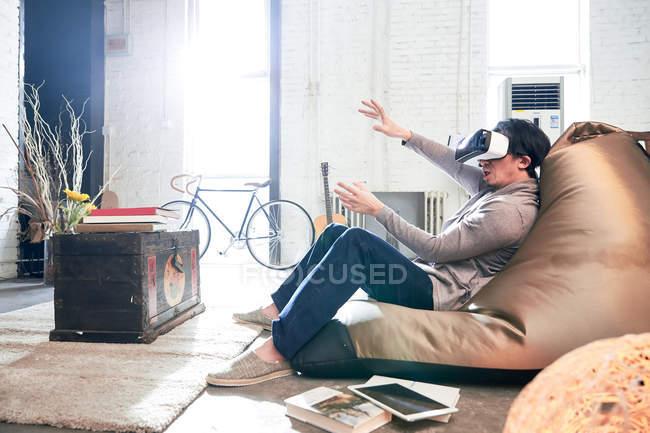 Vista laterale dell'uomo seduto sulla sedia sacchetto di fagioli e utilizzando cuffia realtà virtuale a casa — Foto stock