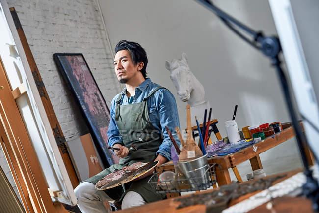 Низький кут зору вдумливого чоловічого художника Холдинг палітри і дивлячись на мольберт в студії — стокове фото