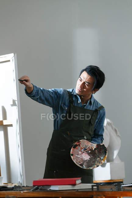 Орієнтовані чоловічого художника Холдинг палітри та живопису малюнок в студії — стокове фото