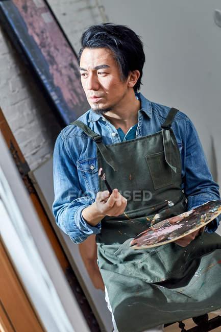Artista chino pensativo sosteniendo paleta y pincel - foto de stock
