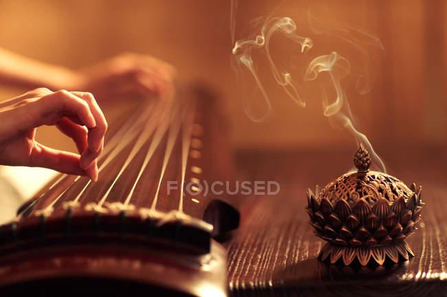 Обрезанный снимок женщины, играющей на традиционном китайском гучженском инструменте — стоковое фото