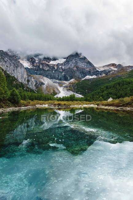 Amazing rocky mountains, green trees and cloudy sky reflected in calm lake water — стокове фото