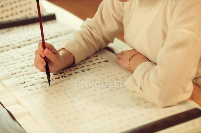 Зламаний постріл жінки, яка пише китайські ієрогліфи з пензлем. — стокове фото
