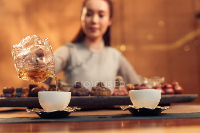 Close-up view of young asian woman pouring tea into cup — Stock Photo