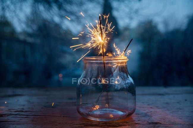 Vue rapprochée du bocal en verre avec des étincelles brûlantes sur fond festif flou — Photo de stock
