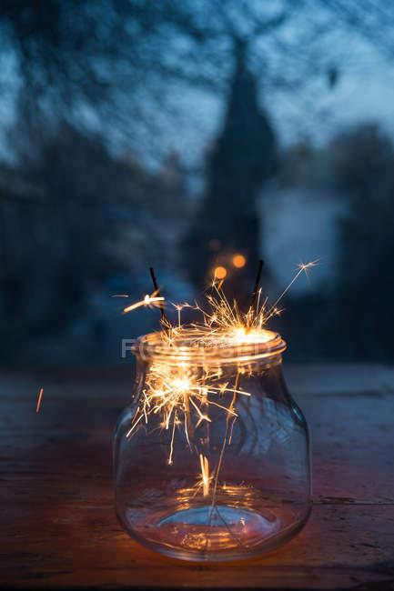 Вигляд скляної банки з палаючими ігриками на розмитому святковому тлі — стокове фото