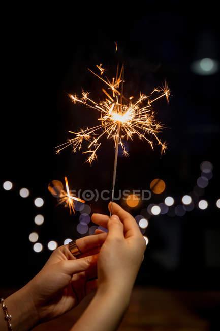 Cropped shot of person holding burning sparkler on blurred festive background — Stock Photo