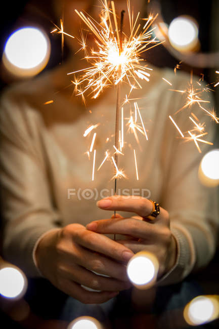 Cropped shot of person holding burning sparkler on blurred festive background — Stock Photo