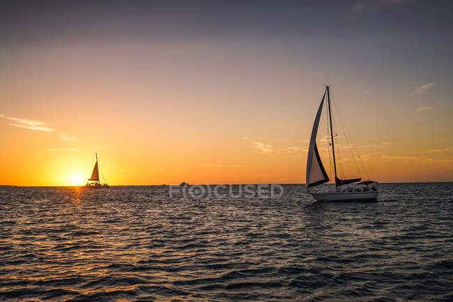 Sail boats floating on wavy sea during scenic sunset — Stock Photo