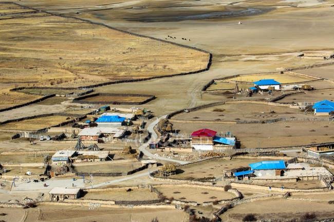 Повітряний вид будинків у долині та пасовищах удень, Тибет. — стокове фото