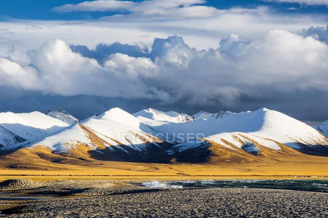Paysage étonnant avec des montagnes enneigées et la vallée sous le ciel nuageux, Tibet — Photo de stock