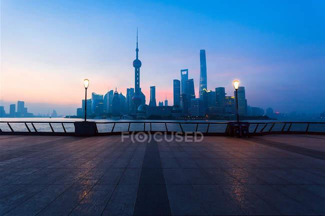 Міська архітектура з сучасними будівлями і хмарочосами на заході сонця, Шанхай — стокове фото