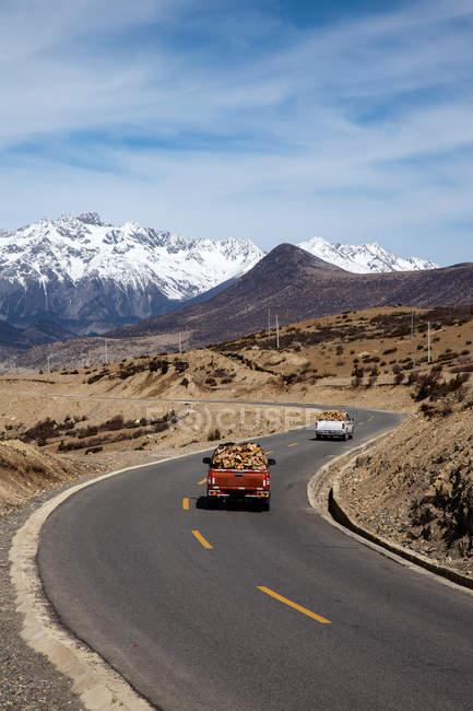 Високий кут огляду автомобілів, що їздять по асфальтній дорозі між мальовничими горами в денний час. — стокове фото