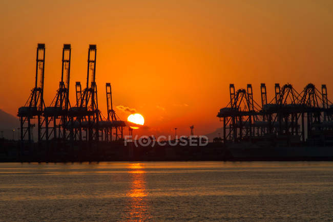 Industrial equipment and ships in harbor at sunset, Shenzhen, China — Stock Photo