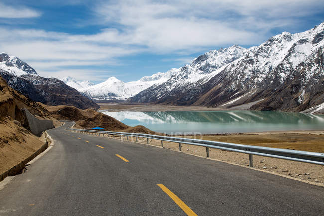 Empty road, snow-covered mountains and beautiful lake in Tibet — Stock Photo