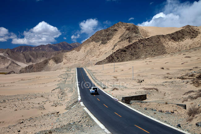 High angle view of car driving on asphalt road between scenic hills during daytime — Stock Photo
