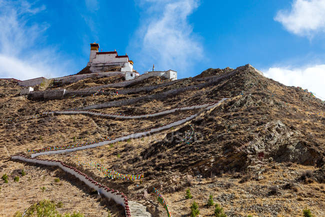 Low angle view of pedestrian walkway and building on rocky mountain at Tibet — Stock Photo
