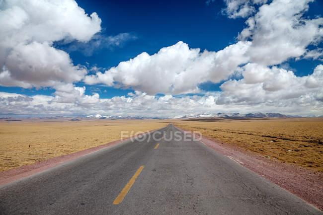 Empty road on Qinghai-Tibet Highway and mountains on horizon — Stock Photo