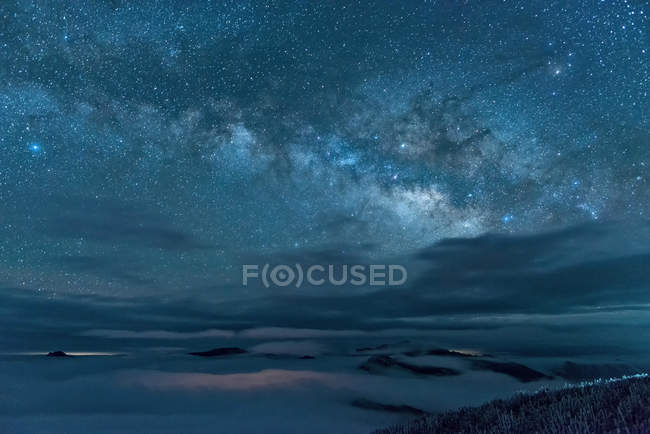 Amazing snow-covered mountains and majestic starry sky at night time — Stock Photo
