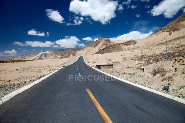 Empty asphalt road in mountain valley at sunny day, Tibet — Stock Photo