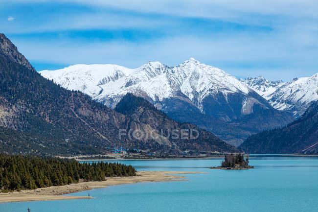 Schöne Landschaft mit schneebedeckten Bergen, ruhigem blauen See und grünen Bäumen in Tibet — Stockfoto