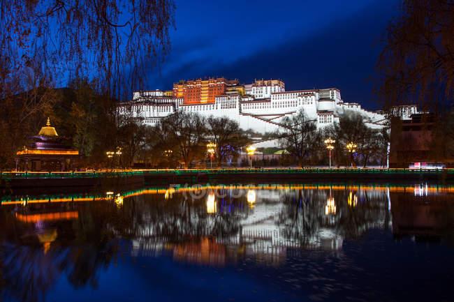 Étonnante architecture antique reflétée dans l'eau calme la nuit, Tibet — Photo de stock