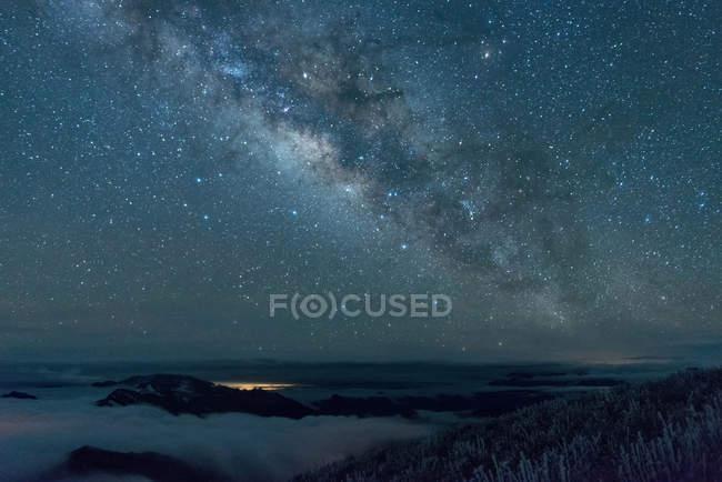 Montagnes enneigées étonnantes et ciel étoilé majestueux la nuit — Photo de stock
