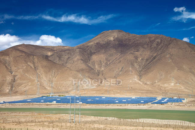 Beautiful landscape with mountains and solar panels at sunny day — Stock Photo