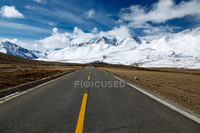 Порожня асфальтова дорога і красиві засніжені гори в Тибеті — стокове фото