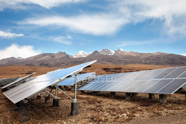 Solar panels in valley and beautiful mountains on horizon — Stock Photo