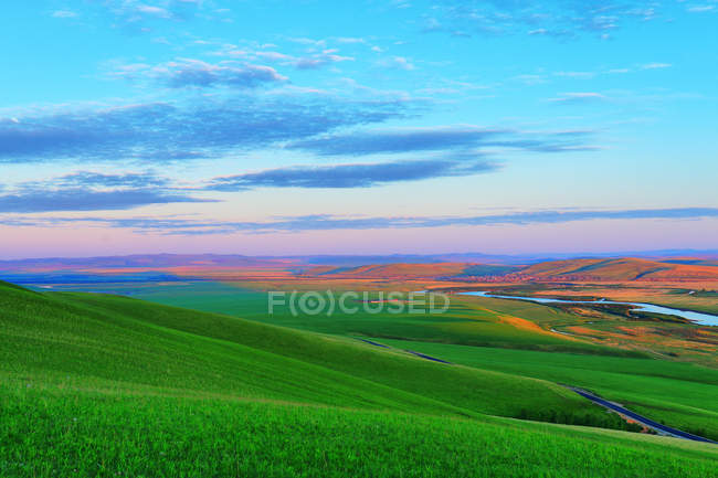Amazing landscape with grassy hills and river in valley during sunset — Stock Photo