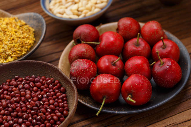 Nahaufnahme nasser reifer roter Äpfel und verschiedener Körner in Schalen auf Holztisch — Stockfoto