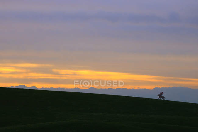 Beautiful landscape with sunrise on grassland and silhouettes of mountains — Photo de stock