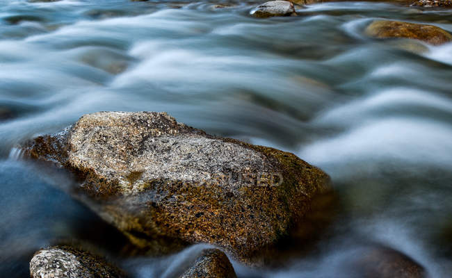 Vista de cerca de las piedras en el agua de corriente rápida en el Tíbet - foto de stock