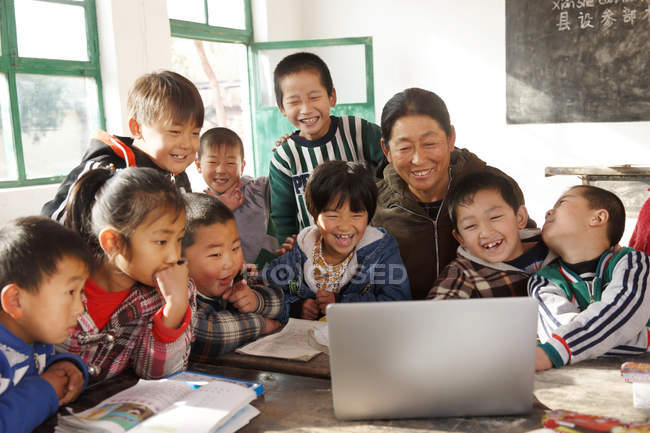 Rural female teacher and pupils using laptop computer together in school — Stock Photo