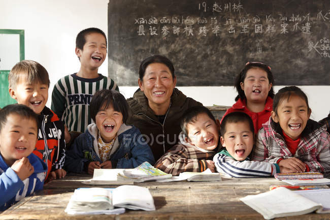Rural female teacher and happy chinese pupils in classroom — Stock Photo