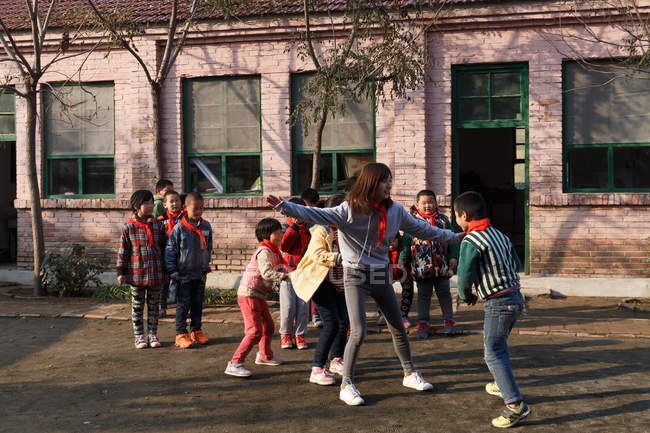 Rural female teacher and happy pupils playing together at school yard — Stock Photo