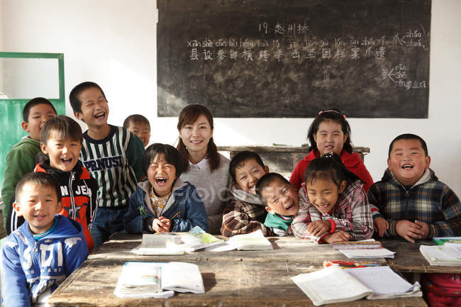 Rural female teacher and happy chinese pupils in classroom — стокове фото
