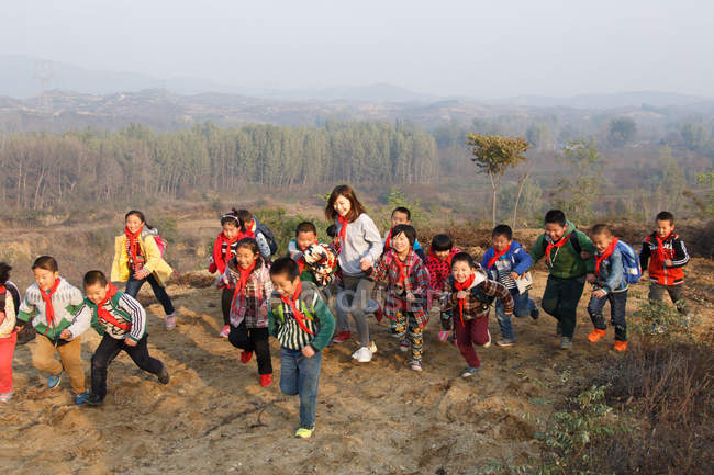 Young female teacher and happy chinese school students playing outdoor — стокове фото