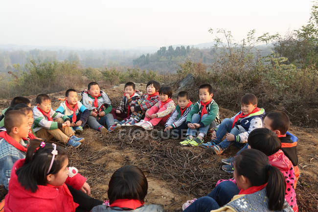 Rural chinese pupils sitting on ground and playing outdoors — стокове фото